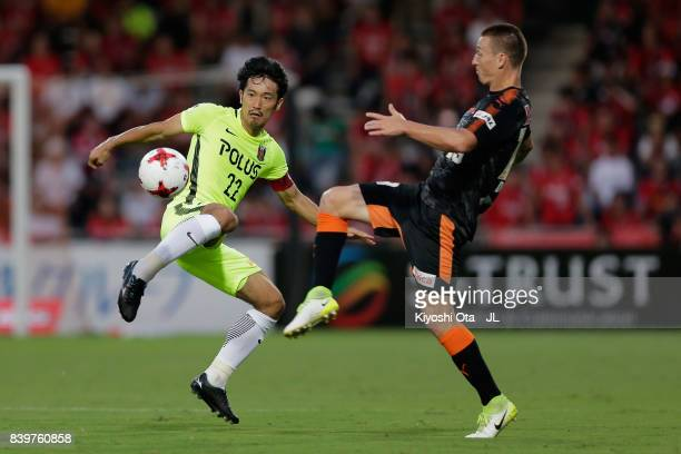 Yuki Abe of Urawa Red Diamonds and Mitchell Duke of Shimizu SPulse compete for the ball during the JLeague J1 match between Shimizu SPulse and Urawa...