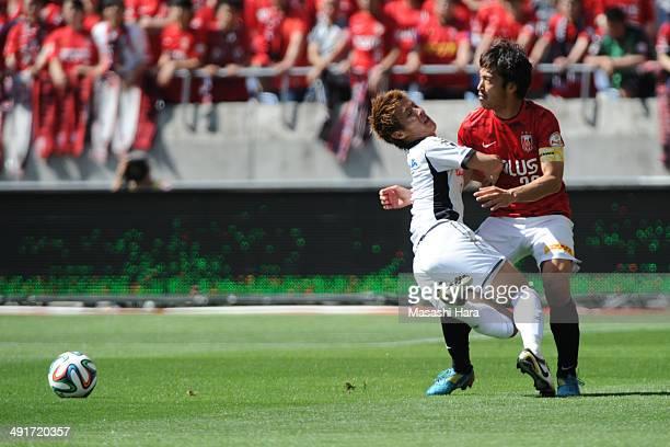 Yuki Abe of Urawa Red Diamonds and Yoichiro Kakitani of Cerezo Osaka compete for the ball during the JLeague match between Urawa Red Diamonds and...