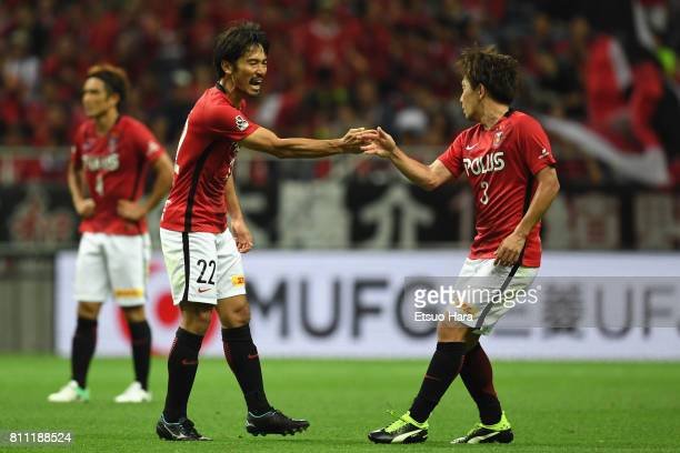 Yuki Abe of Urawa Red Diamonds celebrates scoring his side's first goal with his team mate Tomoya Ugajin during the JLeague J1 match between Urawa...