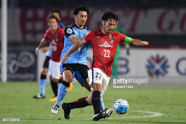 Yuki Abe of Urawa Red Diamonds controls the ball under pressure of Akihiro Ienaga of Kawasaki Frontale during the AFC Champions League quarter final...
