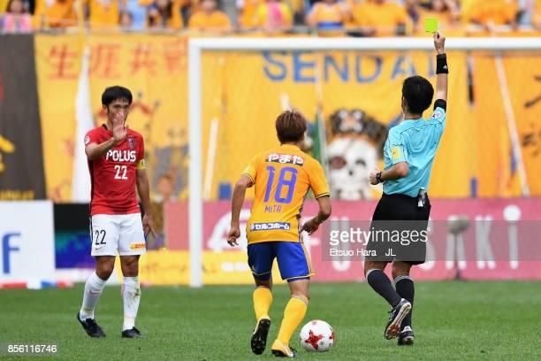 Yuki Abe of Urawa Red Diamonds is shown a yellow card by referee Yusuke Araki during the JLeague J1 match between Vegalta Sendai and Urawa Red...