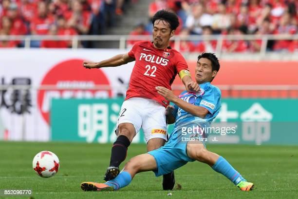 Yuki Abe of Urawa Red Diamonds is tackled by Riki Harakawa of Sagan Tosu during the JLeague J1 match between Urawa Red Diamonds and Sagan Tosu at...
