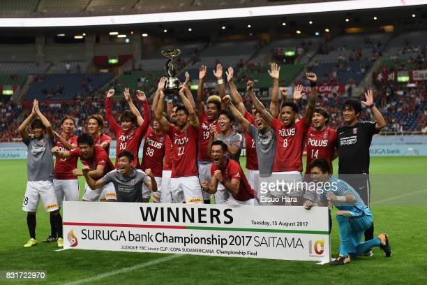 Yuki Abe of Urawa Red Diamonds lifts the trophy after the Suruga Bank Championship match between Urawa Red Diamonds and Chapecoense at Saitama...