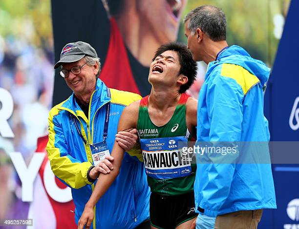 Yuki Kawauchi of Japan is assisted after he crossed the finish line during the TCS New York City Marathon on November 1 2015 in New York City
