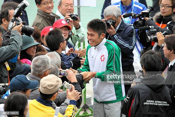 Yuki Kawauchi of Japan is surrounded by fans after the Fukuoka International Marathon at Heiwadai Athletic Stadium on December 4 2011 in Fukuoka Japan
