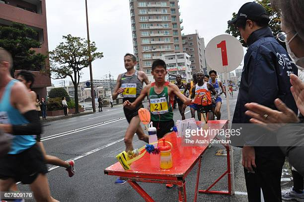Yuki Kawauchi of Japan picks up his bottle in the Fukuoka International Marathon on December 4 2016 in Fukuoka Japan