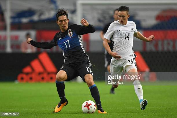 Yuki Kobayashi of Japan controls the ball under pressure of Ryan Thomas of New Zealand during the international friendly match between Japan and New...