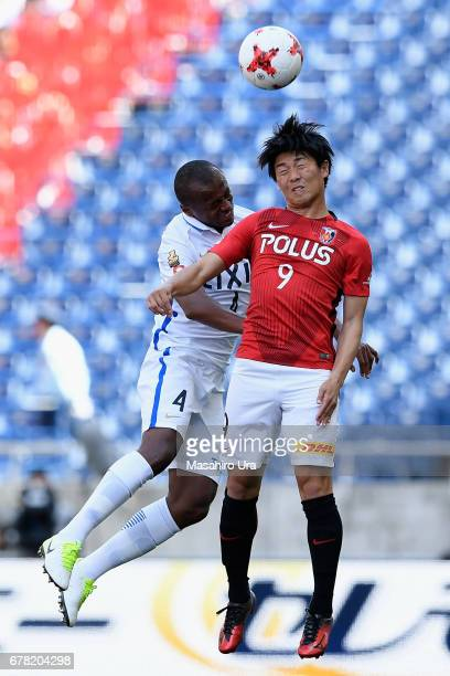 Yuki Muto of Urawa Red Diamonds and Leo Silva of Kashima Antlers compete for the ball during the JLeague J1 match between Urawa Red Diamonds and...
