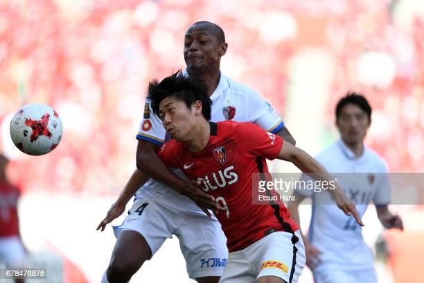 Yuki Muto of Urawa Red Diamonds and Leo Silva of Kashima Antlers compete for te ball during the JLeague J1 match between Urawa Red Diamonds and...
