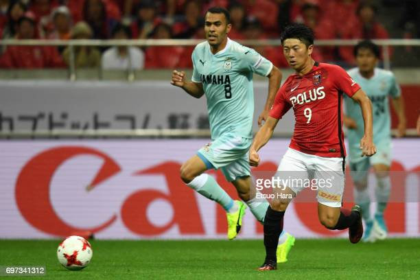Yuki Muto of Urawa Red Diamonds and Musaev of Jubilo Iwata compete for the ball during the JLeague J1 match between Urawa Red Diamonds and Jubilo...