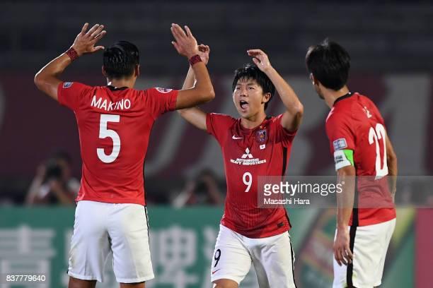 Yuki Muto of Urawa Red Diamonds celebrates scoring his side's first goal with his team mates Tomoaki Makino and Yuki Abe during the AFC Champions...