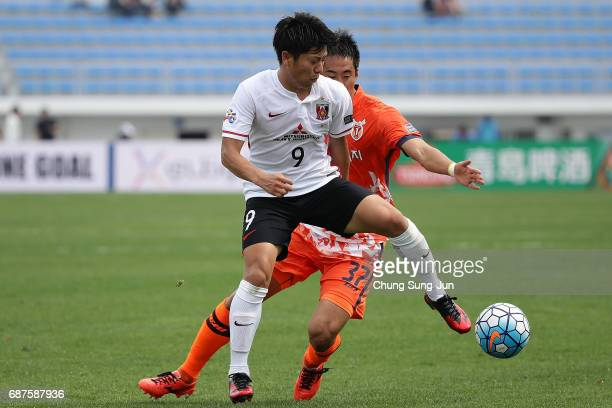 Yuki Muto of Urawa Red Diamonds competes for the ball with Kim WonIl of Jeju United FC during the AFC Champions League Round of 16 match between Jeju...