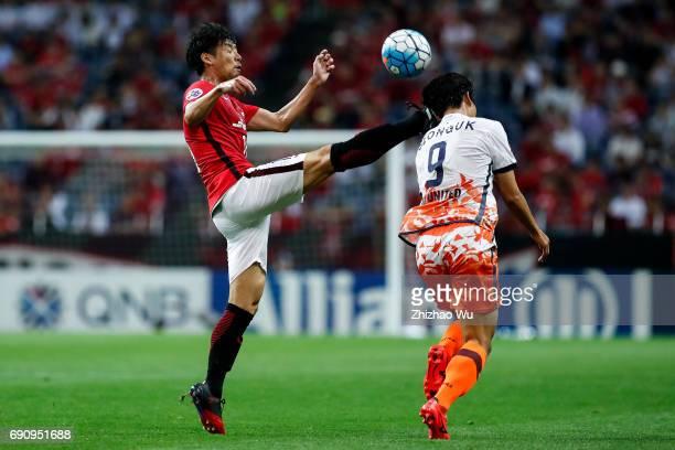 Yuki Muto of Urawa Reds Diamonds defends Jim Seonguk of Jeju United during the AFC Champions League Round of 16 match between Urawa Red Diamonds and...