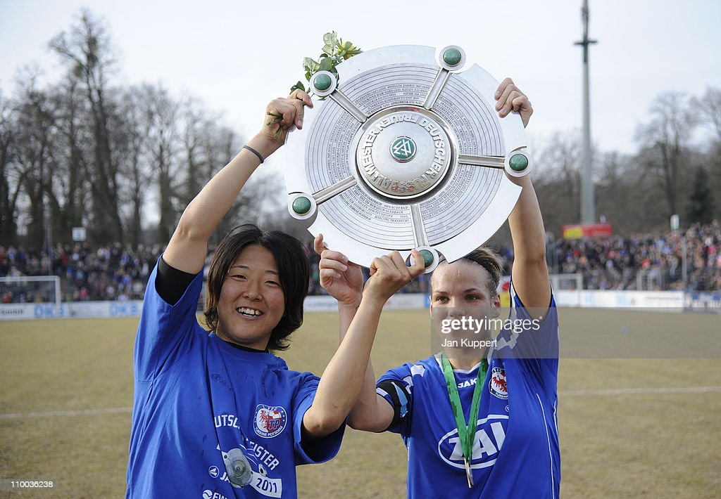 Yuki Nagasato (L) and Isabel Kerschowski (R) celebrate with the trophy after winning the Women Bundesliga match between Turbine Potsdam and Essen-Schoenebeck at the Karl-Liebknecht stadium on March 13, 2011 in Potsdam, Germany.