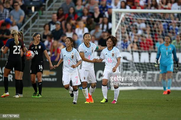 Yuki Ogimi of Japan celebrates her goal against Hope Solo of United States of America with Mana Iwabuchi of Japan as Morgan Brian and Allie Long of...