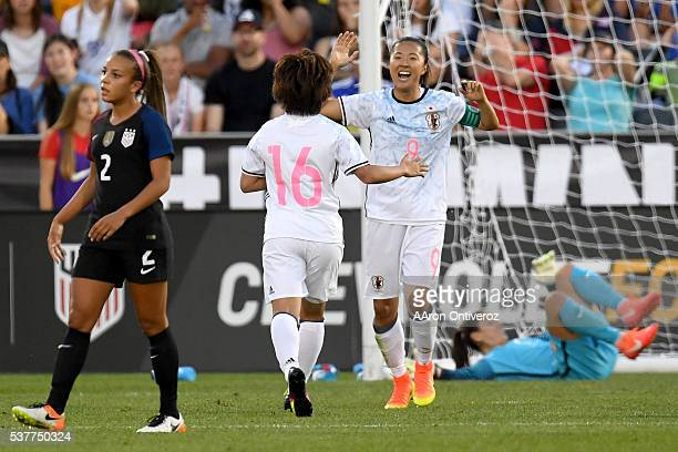 Yuki Ogimi of Japan celebrates her goal with Mana Iwabuchi of Japan as Hope Solo of US Women's National Team lies on the turf during the first half...