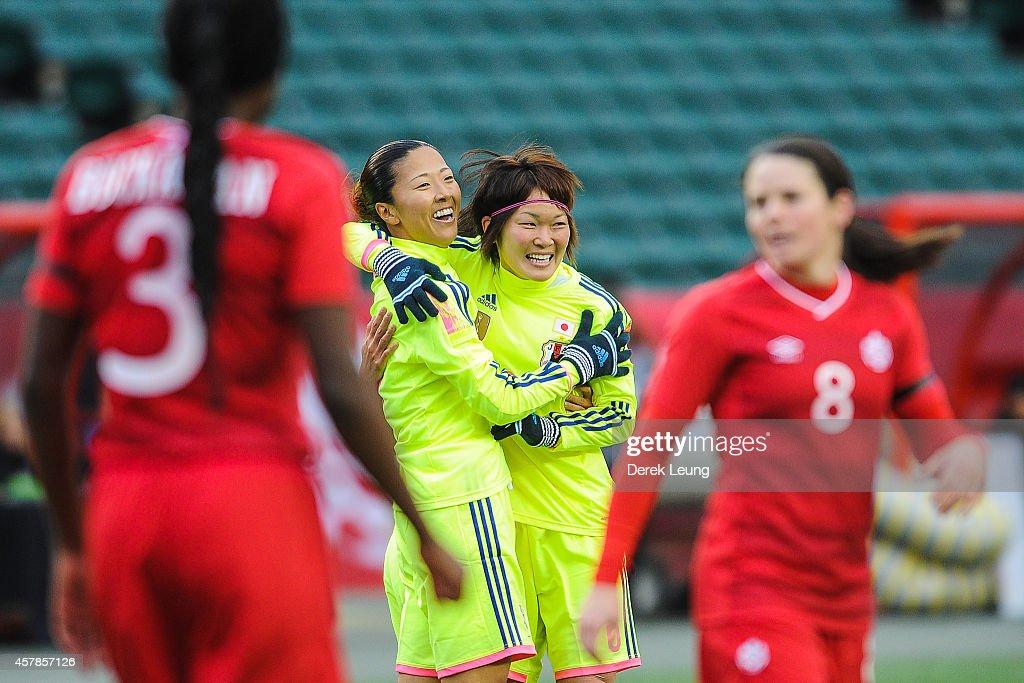 Yuki Ogimi (L) of Japan celebrates scoring her team's first goal with her teammate Mizuho Sakaguchi during a match at Commonwealth Stadium on October 25, 2014 in Edmonton, Alberta, Canada.