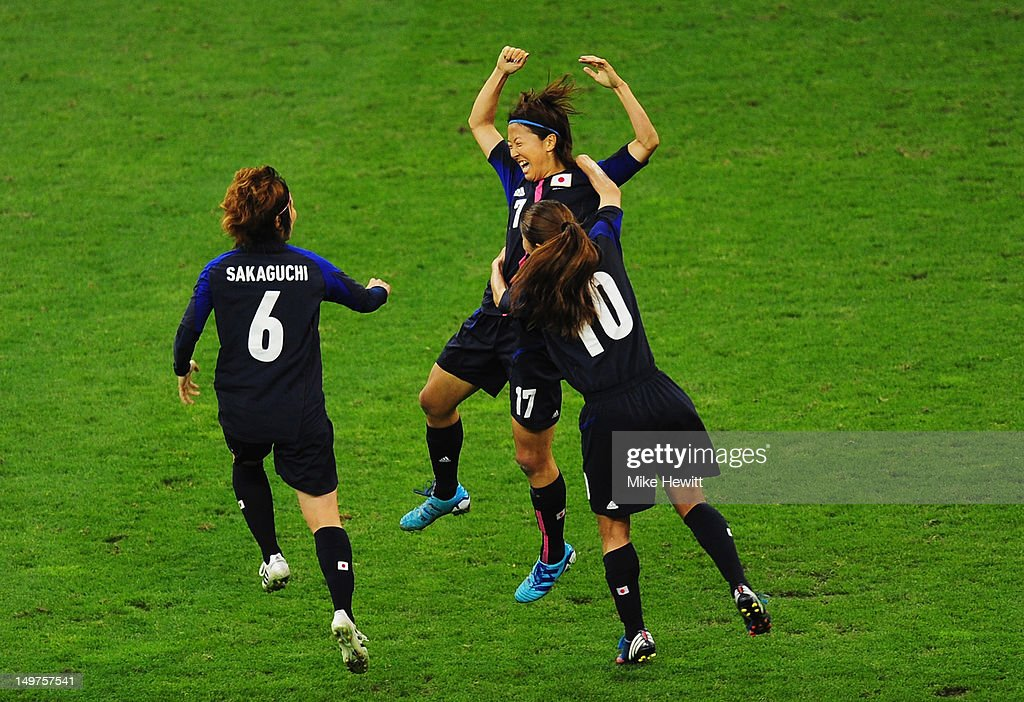 Yuki Ogimi of Japan celebrates with team mates Mizuho Sakaguchi #6 and Homare Sawa of Japan after scoring the opening goal during the Women's Football Quarter Final match between Brazil and Japan, on Day 7 of the London 2012 Olympic Games at Millennium Stadium on August 3, 2012 in Cardiff, Wales.