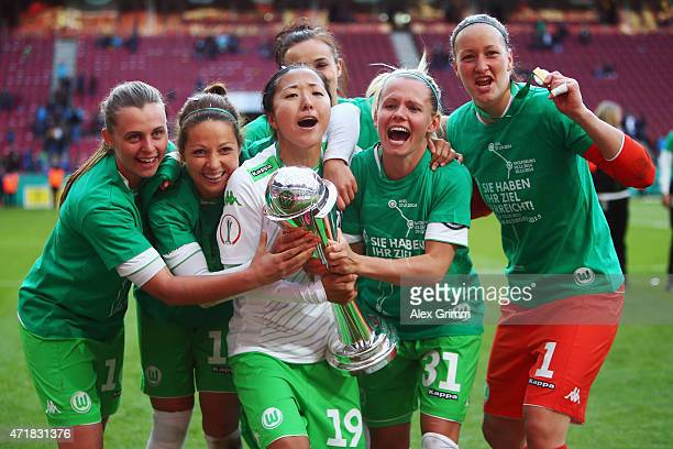 Yuki Ogimi of Wolfsburg and team mates celebrate with the trophy after winning the Women's DFB Cup Final between Turbine Potsdam and VfL Wolfsburg at...