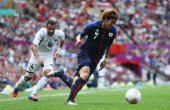 Yuki Otsu of Japan and Hassan Hossam of Egypt compete for the ball during the Men's Football Quarter Final match between Japan and Egypt on Day 8 of...