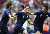Yuki Otsu of Japan celebrates with his team mates after scoring his team's first goal during the Men's Football Semi Final match between Mexico and...