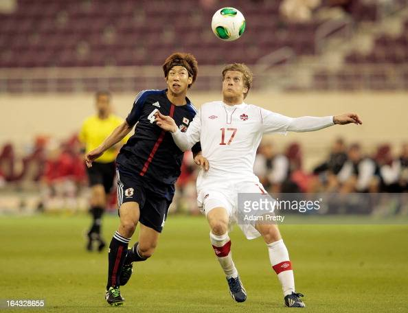 Yuki Otsu of Japan challenges Marcel De Jong of Canada during the international friendly match between Japan and Canada at Khalifa International...