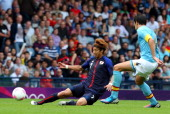 Yuki Otsu of Japan holds off Javier Martinez of Spain during the Men's Football first round Group D Match of the London 2012 Olympic Games between...