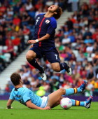 Yuki Otsu of Japan is tackled by Inigo Martinez of Spain during the Men's Football first round Group D Match of the London 2012 Olympic Games between...