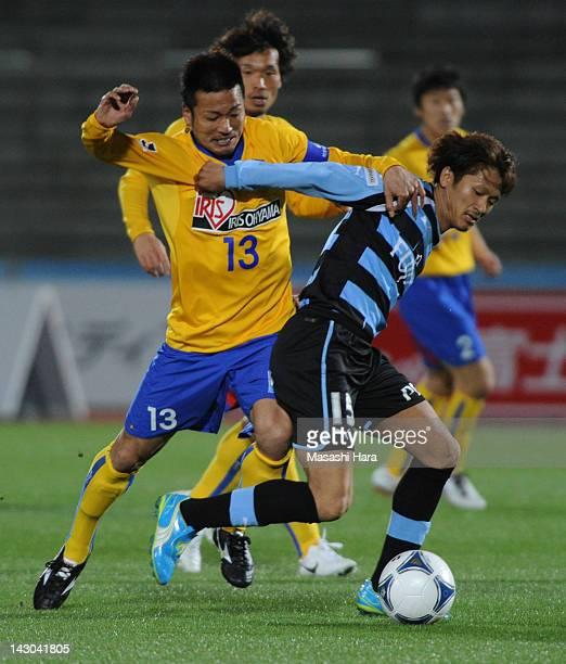 Yuki Saneto of Kawasaki Frontale and Atsushi Yanagisawa of Vegalta Sendai compete during the JLeague Yamazaki Nabisco Cup Group A match between...