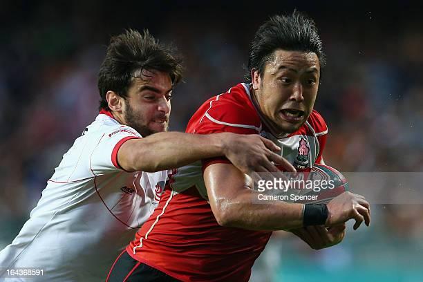 Yuki Shishimoto of Japan is tackled during the match between Georgia and Japan during day two of the 2013 Hong Kong Sevens at Hong Kong Stadium on...