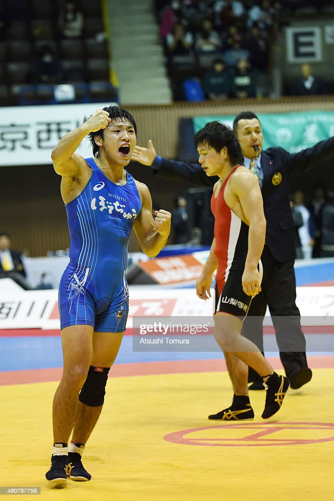 Yuki Takahashi (Red) and Fumitaka Morishita (Blue) compete in Men's 57kg free style final match during 2014 Emperor's Cup All Japan Wresting Championship on December 23, 2014 in Tokyo, Japan.
