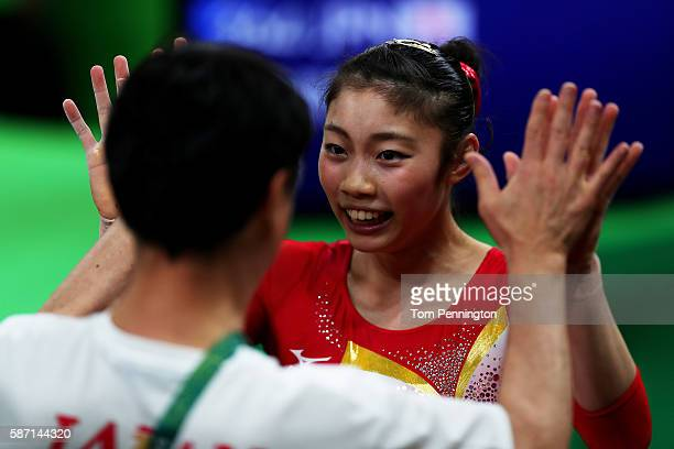 Yuki Uchiyama of Japan high fives with her coach after competing on the balance beam during Women's qualification for Artistic Gymnastics on Day 2 of...