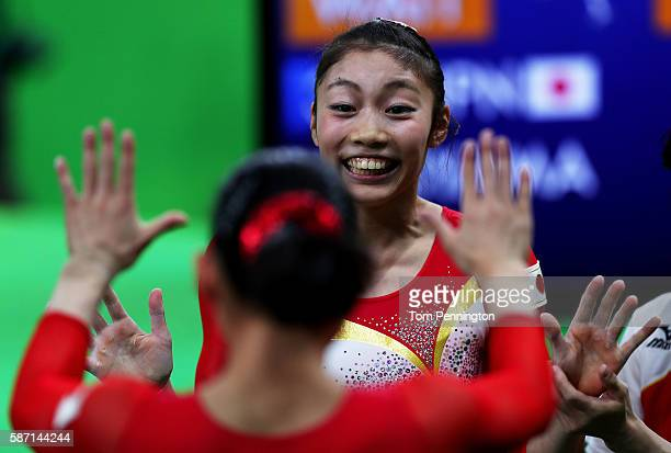 Yuki Uchiyama of Japan high fives with her team mate after competing on the balance beam during Women's qualification for Artistic Gymnastics on Day...