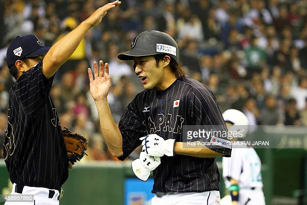 Yuki Yanagita of Samurai Japan celebrates after hitting a triple to center field sending two runners home in the second inning during the game two of...
