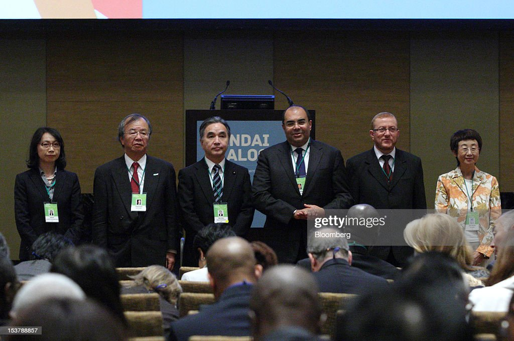 Yukie Osa, a prefessor at Rikkyo University, from left, Yoshiaki Kawata, a professor at Kansai University, Tatsuo Hirano, Japan's reconstruction minister, Mahmoud Mohieldin, managing director of the World Bank Group, Mohamed Najib Boulif, Morocco's general affairs and governance minister, and Emiko Okuyama, mayor of Sendai City, pose for a group photo before the opening plenary at the Sendai Dialogue on the sidelines of the Annual Meetings of the International Monetary Fund (IMF) and the World Bank Group in Sendai City, Miyagi Prefecture, Japan, on Tuesday, Oct. 9, 2012. The world's finance ministers and central bank governors are gathered in Tokyo for the annual meetings of the IMF and the World Bank as the rebound from the deepest global recession since World War II stagnates. Photographer: Tomohiro Ohsumi/Bloomberg via Getty Images