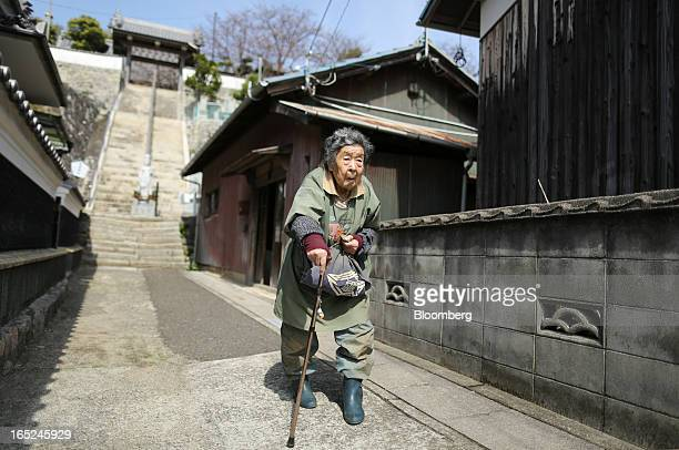 Yukiko Watanabe uses a walking stick as she walks through her neighborhood on Gogo Island in Matsuyama Ehime Prefecture Japan on Friday March 22 2013...