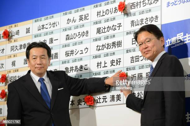 Yukio Edano head of the Constitutional Democratic Party of Japan left and Akira Nagatsuma deputy chairman place a red paper rose on a candidate's...