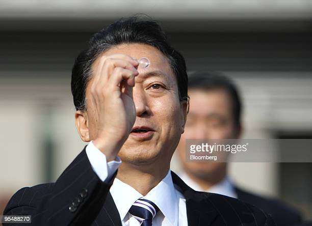 Yukio Hatoyama Japan's prime minister center looks at a condenser manufactured by Murata Manufacturing Co following a news conference announcing the...