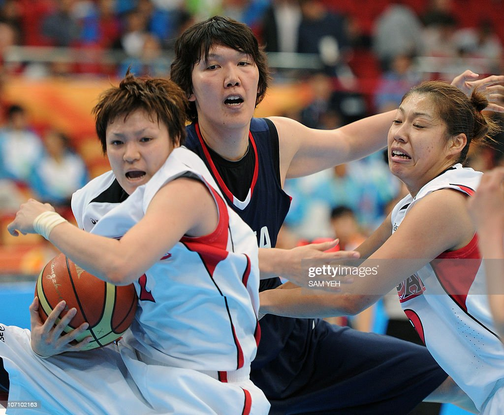 Yuko Oga of Japan competes against Kim KweRyong of South Korea at the women's basketball semifinal match during the 16th Asian Games in Guangzhou on...