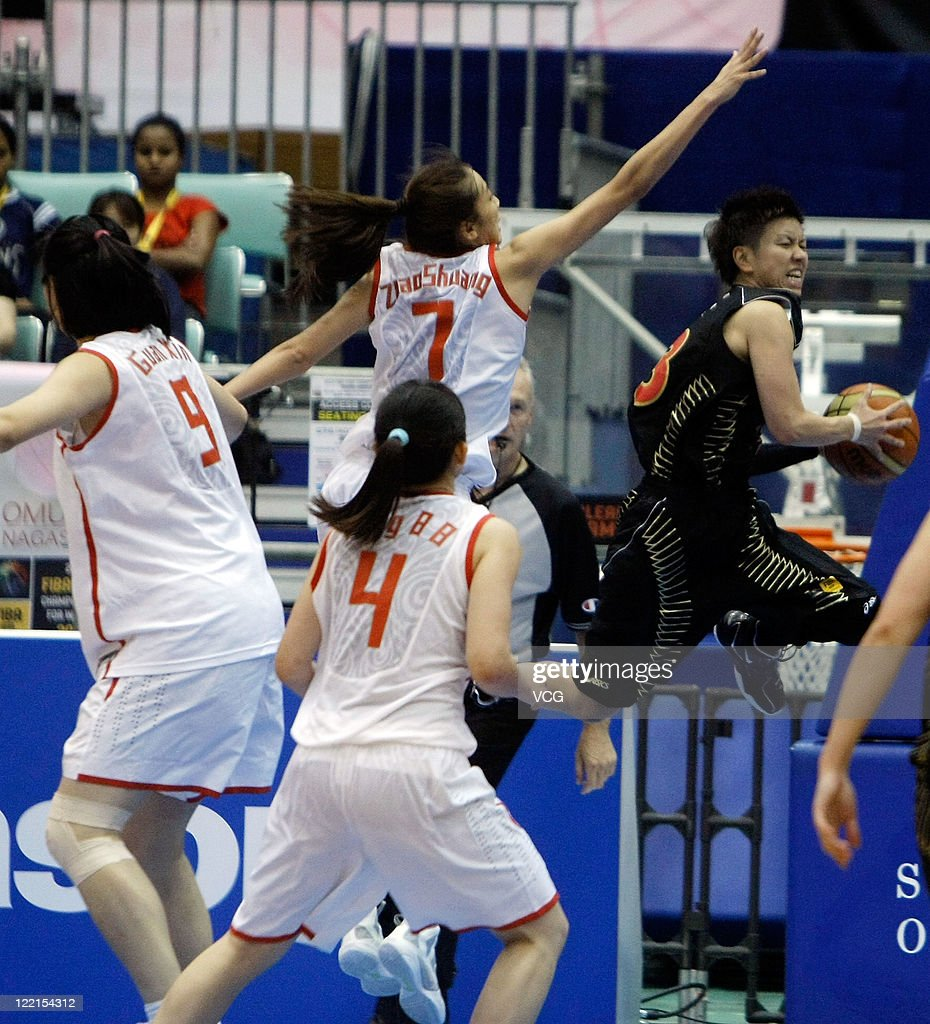 Yuko Oga of Japan drives the ball past Zhao Shuang of China in the group match during the 2011 FIBA Asia Championship For Women at Sea Hat on August...
