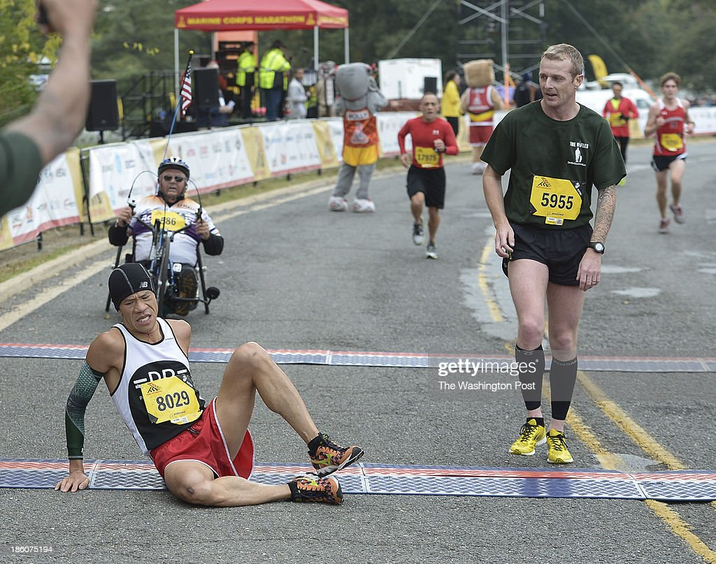 Yukun Fung, of Aspen Hill, Md., falls to the ground at the finish line during the 38th Marine Corps Marathon on Sunday, October 27, 2013.