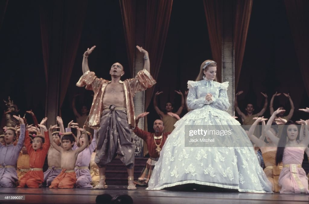 Yul Brenner performing on stage with the Broadway cast of 'The King and I' in 1977.