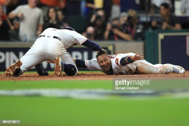 Yuli Gurriel of the Houston Astros celebrates with teammate Carlos Correa after scoring off of a double hit by Brian McCann against Tommy Kahnle of...