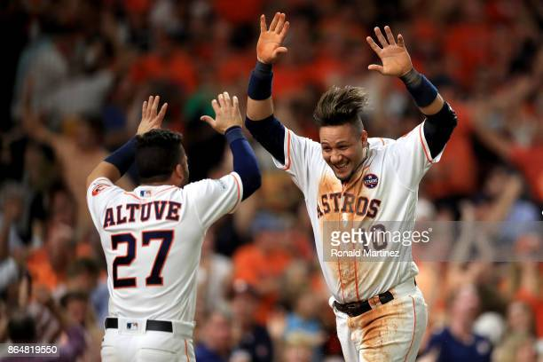 Yuli Gurriel of the Houston Astros celebrates with teammate Jose Altuve after scoring off of a double hit by Brian McCann against Tommy Kahnle of the...