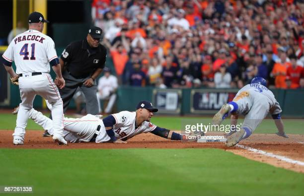 Yuli Gurriel of the Houston Astros dives to tag first base for the out as Chris Taylor of the Los Angeles Dodgers slides during the seventh inning in...