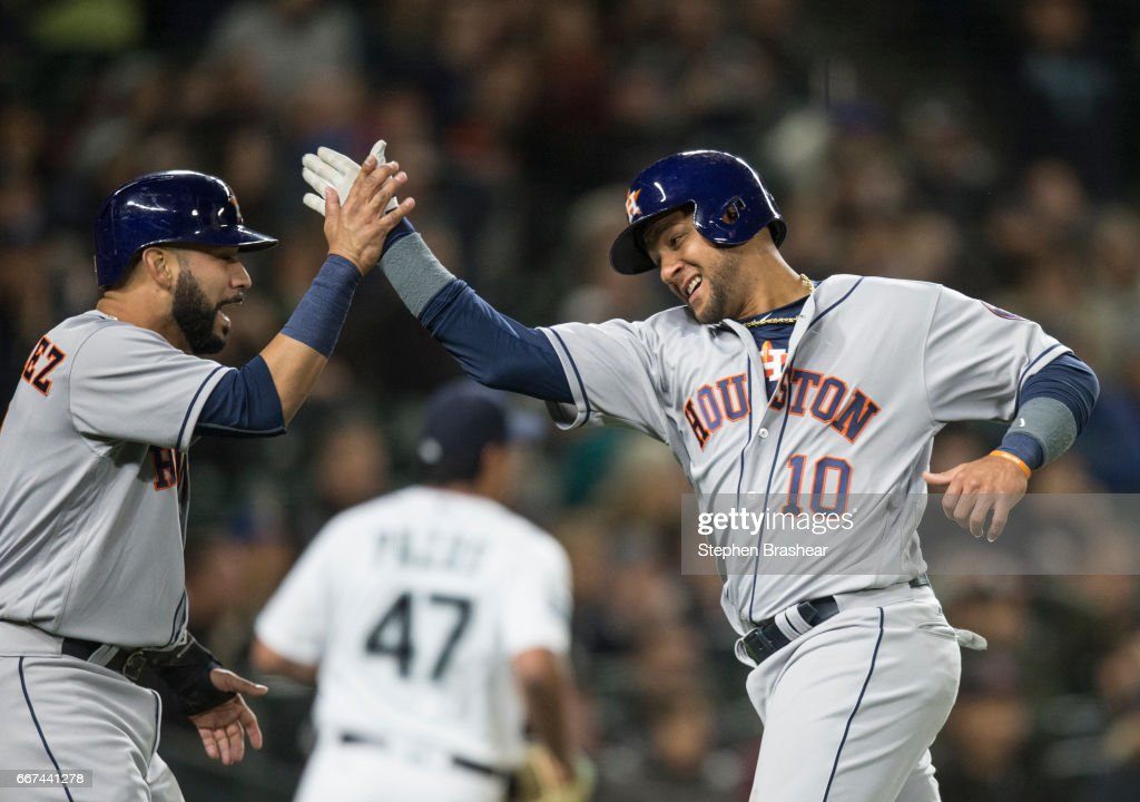 Yuli Gurriel #10, right, of the Houston Astros and Marwin Gonzalez #9 of the Houston Astros celebrate scoring on a three-run double by Evan Gattis #11 of the Houston Astros off of James Pazos #47 of the Seattle Mariners during the sixth inning of game at Safeco Field on April 11, 2017 in Seattle, Washington. Brian McCann #16 of the Houston Astros also scored on the play.