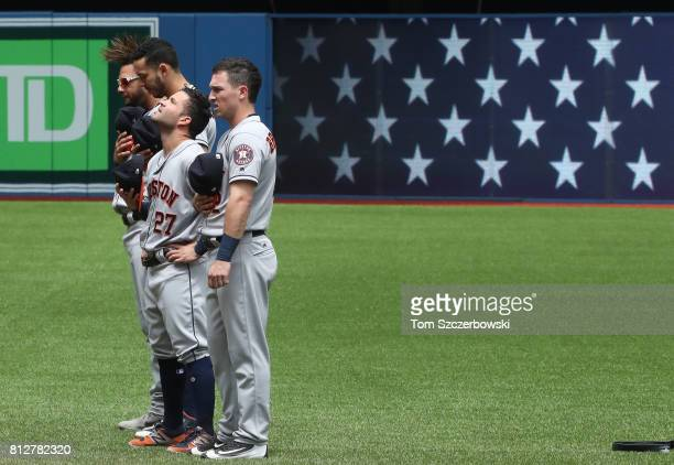 Yulieski Gurriel of the Houston Astros and Carlos Correa and Jose Altuve and Alex Bregman stand for the playing of the American national anthem...