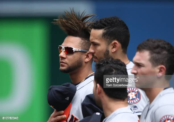 Yulieski Gurriel of the Houston Astros and Carlos Correa and Jose Altuve and Alex Bregman stand for the playing of the anthems before the start of...
