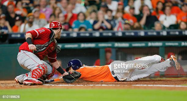 Yulieski Gurriel of the Houston Astros scores in the third inning on a sacrifice fly ball by Evan Gattis as Jett Bandy of the Los Angeles Angels of...
