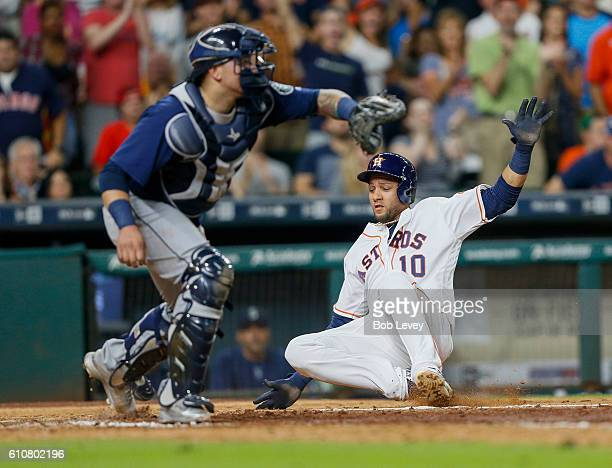 Yulieski Gurriel of the Houston Astros slides safely at home before Jesus Sucre of the Seattle Mariners can apply the tag in the sixth inning at...